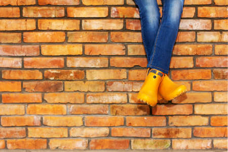 cross-legged sitting on a brick wall of a young girl in jeans and orange galoshes against the background of a brick wall with a copy space Stock Photo