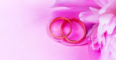 a pair of gold wedding rings with a pink peony flower on a pink background with a copy space Stock Photo