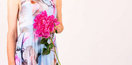 a young woman in a colorful dress with a peony flower in her hand on a light pink background with a copy space