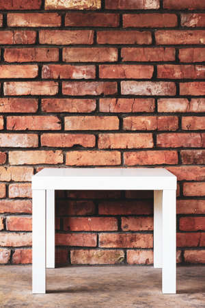 an empty white table against a brick wall Stock Photo