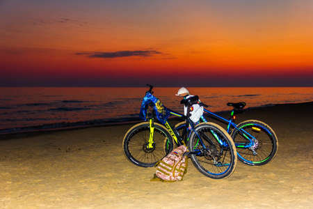 Anapa, Russia - July 03, 2020: two bicycles stand on a sandy beach by the sea at sunset Editorial