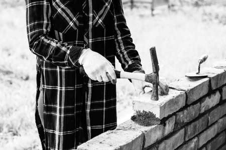 young woman builds a wall of bricks, lays a brick on a cement-sand mortar, tapping a brick with a hammer, black and white photo Stock Photo