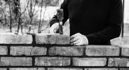 a man builds a wall of bricks, lays a brick on a cement-sand mortar, tapping a brick with a hammer, black and white photo Stock Photo
