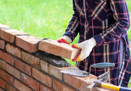 young woman builds a wall of bricks, lays bricks on cement-sand mortar Stock Photo