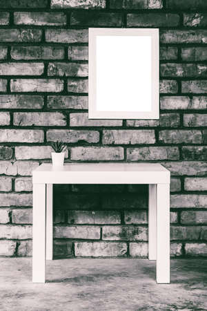 minimalistic loft-style interior with a white table, mock up white picture frame or photo frame on a brick wall, black and white photo
