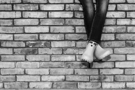 crossed legs of a young girl in jeans and orange galoshes sitting on a brick wall against a brick wall background with copy space, black and white photo