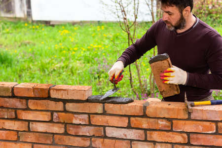 a man builds a wall of bricks, lays a brick on a cement-sand mortar Stock Photo