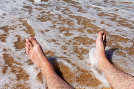 men's legs on a sandy beach in the sea waves Stock Photo