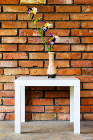 an iris flower in a vase on a white table against a brick wall background Stock Photo