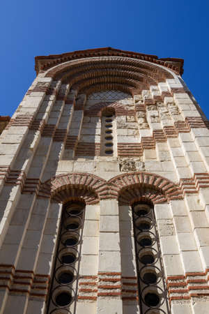 the wall of the ancient Byzantine Orthodox Church against the blue sky, bottom view
