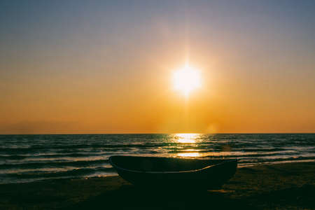 seascape with a boat on the shore against the sunset