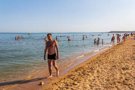 Kerch, Russia - 13 August 2019: vacationers and tourists swim in the Black Sea and sunbathe and relax on the beach on the beach on a summer day
