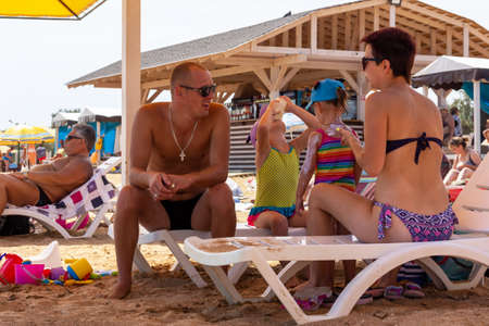Kerch, Russia - 13 August 2019: a young family is resting at the sea, a husband, a wife and two little daughters on sun loungers on the sea beach, a young mother smears a girl with sun cream Editorial