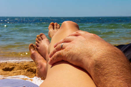 a man and a woman are sunbathing on the sea beach, a man's hand with a gold wedding ring lies on the woman's hip against a blue sea background Stock Photo
