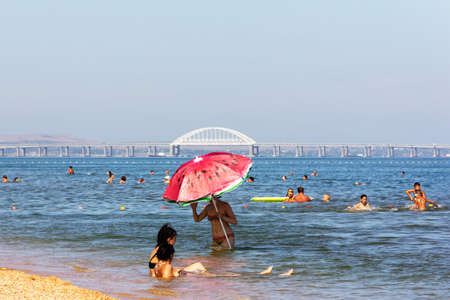 Kerch, Russia - 13 August 2019: A young woman with a large umbrella and other vacationers and tourists swim in the sea against the background of the Crimean bridge on a summer day