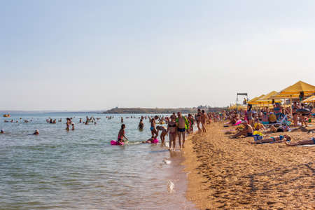 Kerch, Russia - 13 August 2019: vacationers and tourists swim in the black sea and sunbathe and relax on the beach on a summer day Editorial