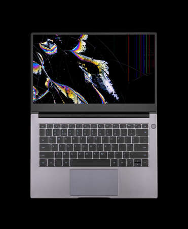 open laptop with a broken screen in color spots and cracks isolated on black background close up top view Stock Photo