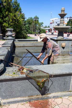 Kerch, Russia - 13 August 2019: a utility worker cleans the pool from garbage in the city center on a summer day