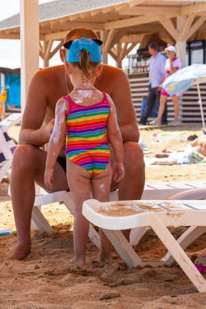 dad smears his little daughter with sun cream on the beach
