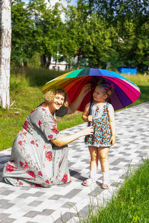 mom and daughter with a rainbow umbrella walking in the park on a sunny summer day
