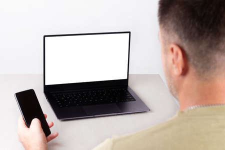 a man with a phone in his hand is sitting in front of a laptop with a white mockup on the monitor, the concept of office work, remote work, marketing, training, coaching