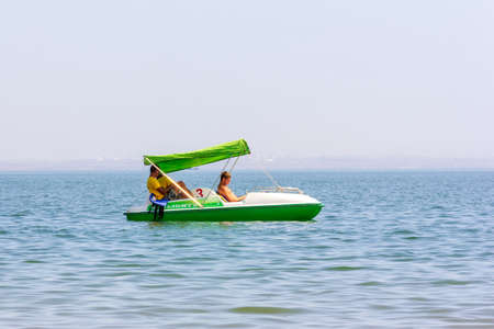 Kerch, Russia - 13 August 2019: three young lifeguard guys on a white and green catamaran are slowly floating on the sea water on a summer day Editorial