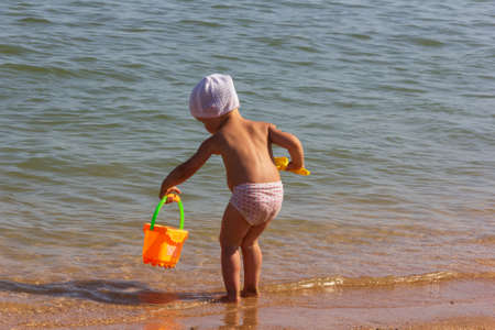 a little girl with a toy bucket and a shovel plays on the sandy beach on a summer day Stock Photo