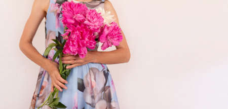 a young woman in a colorful dress with a bouquet of peony flowers in her hands on a light pink background with a copy space