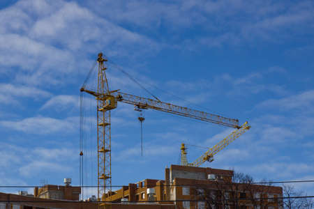 Crane and building construction site against blue sky. Stock Photo