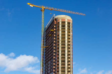 reinforcement: Crane and building construction site against blue sky. Stock Photo