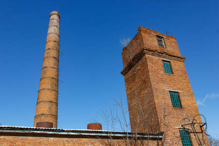 tall chimney: Old tower and pipe production on the background of blue sky