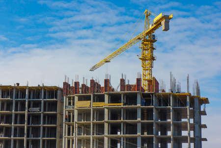 Crane and building construction site against blue sky. Stock Photo