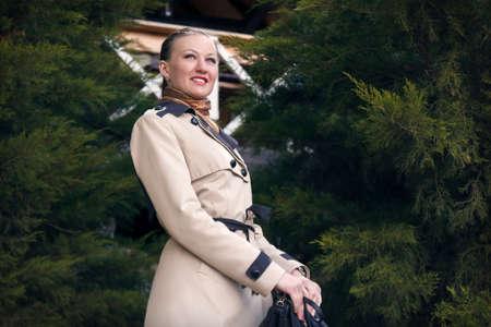 Happy girl in the coats at ulybvaetsja amid green trees Stock Photo