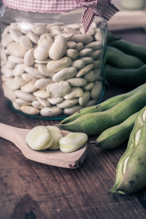 Broad Beans on a wooden Table with Jar, full of dry beans photo