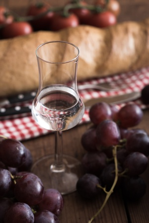 Glass of Grappa with Grape, Bread and Tomatoes on a wooden Table
