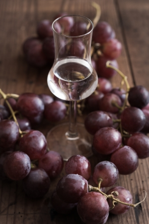 Glass of Grappa with Grape on a wooden Table