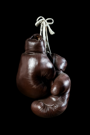 boxing ring: old Boxing Gloves, hanging, isolated on black Background