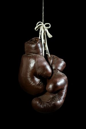 old Boxing Gloves, hanging, isolated on black Background photo