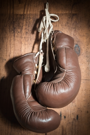 old Boxing Gloves hanging on wooden wall photo