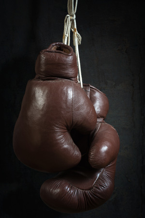 old used boxing Gloves, hanging before a dirty Wall photo