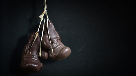 old used boxing Gloves, hanging before a Chalk Board