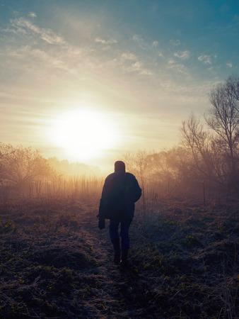 hombre solo: El hombre va en contra de la salida del sol