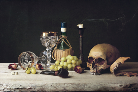 Vanitas witch Skull; Pipe, dice; wine glass, wine and grape photo