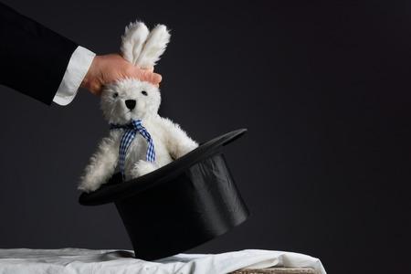 mago: Hombre en el juego que saca un conejo de la chistera topper Foto de archivo
