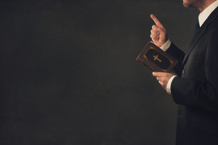 A standing man in Suit with a Bible and a wagging finger