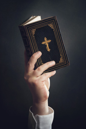 spiritually: Man is holding a Bible in the Air Stock Photo