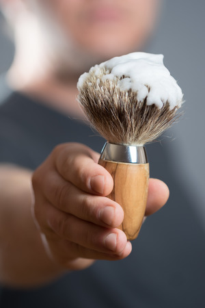 depilate: Man is holding a Shaving Brush in his Hand Stock Photo