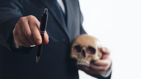 Businessman gives a pen while holding a skull in his hand