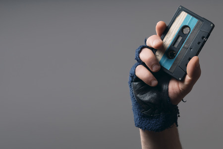 male hand with glove holding an old music tape Standard-Bild