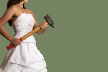 Young confident bride holding a sledgehammer in the hands